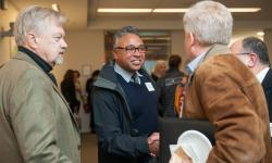 Two men shaking hands with another standing by, networking at an event