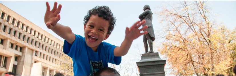 Image of a child with outstretched hands in front of Boston City Hall