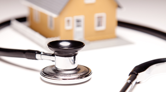 A small house model surrounded by a stethoscope
